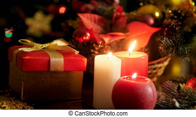 Closeup 4k footage of burning candles and gift box with present for Christmas