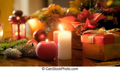 Closeup 4k footage of burning candles and lanterns against traditional wreath and Christmas gifts and presents. Perfect background for winter celebrations and holidays