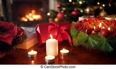 Closeup 4k footage of burning candles, gifts with presents from Santa and advent wreath against Christmas tree and burning firepalce