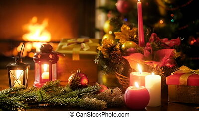 Closeup 4k footage of burning fireplace in living room and beautiful table decorated with candles, baubles and Christmas gifts and presents. Perfect shot for winter celebrations and holidays