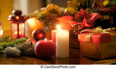 Closeup 4k footage of burning red and white candles on table decorated for Christmas. Perfect background for winter celebrations and holidays