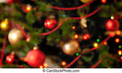Closeup 4k footage of camera defocusing on beautiful Christmas tree with red and golden baublbes and colorful loghts