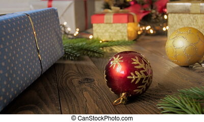 Closeup 4k footage of camera panning over Christmas gifts and colorful baubles on floor
