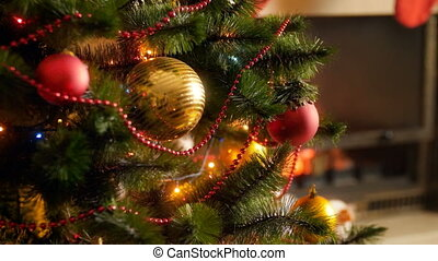 Closeup 4k footage of Christmas tree decorated with baubles, garlands and lights for celebrating New Year against burning fireplace in living room. Perfect shot for winter celebrations and holidays
