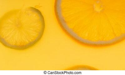 Closeup 4k footage of citrus slices floating in fresh orange...