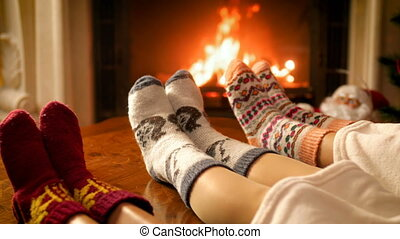 Closeup 4k footage of family feet lying on sofa under blanket warming at burning fireplace