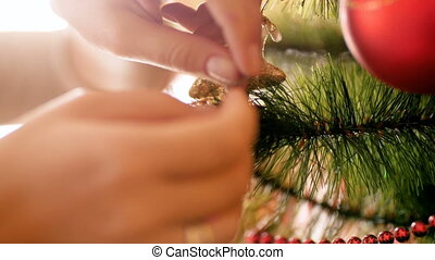 Closeup 4k footage of female hands putting red bauble on Christmas tree. Preparations for winter holidays and celebrations