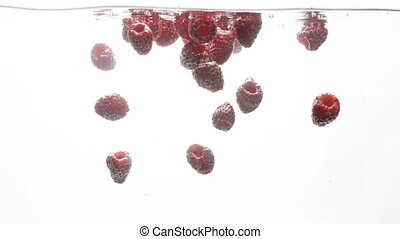 Closeup 4k footage of fresh ripe raspberries falling in...