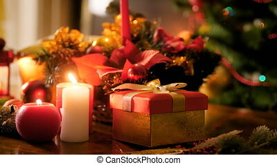 Closeup 4k footage of gift box, burning candles and traditional Christmas wreath on table. Perfect background for winter celebrations and holidays