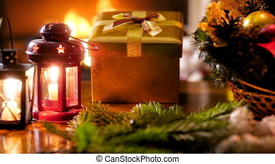 Closeup 4k footage of golden Christmas gift box, candles and...