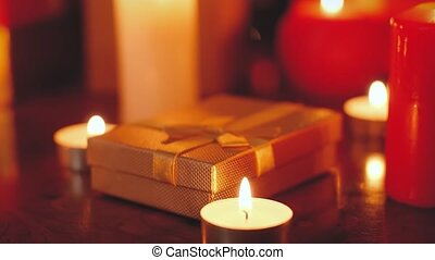Closeup 4k footage of golden gift box and burning candles on wooden table at night. Perfect background or backdrop for Christmas or New Year