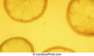 Closeup 4k footage of lemon slice falling in backlit...