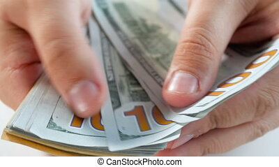 Closeup 4k footage of male finger counting 100 US dollar...