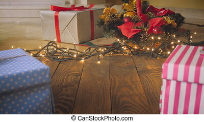 Closeup 4k footage of parents hands putting Christmas gift on floor at living room