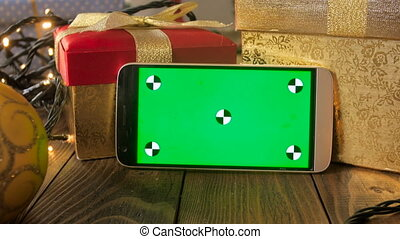 Closeup 4k footage of smartphone leaning on Christmas gift...