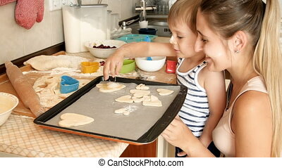Closeup 4k footage of smiling toddler boy with mother making cookies from dough and putting them on baking sheet