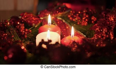 Closeup 4k footage of three red and white candles burning in advent Christmas wreath at night. Perfect background or backdrop for Christmas or New Year