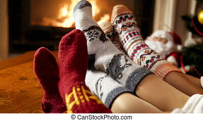 Closeup 4k footage of young family feet in woolen socks lying by the burning fireplace at night