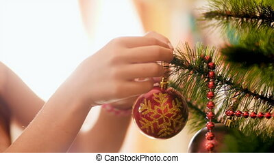 Closeup 4k footage of young girl adorning Christmas tree...