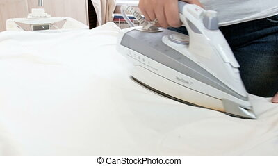 Closeup 4k footage of young housewife ironing white clothes...