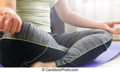 Closeup 4k footage of young slim woman practising yoga at...