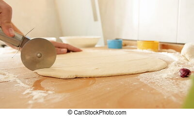 Closeup 4k footage of young woman cutting dough for pie with special round cutter knife