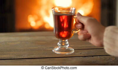 Closeup 4k footage of young woman in sweater drinking hot tea by the burning fireplace
