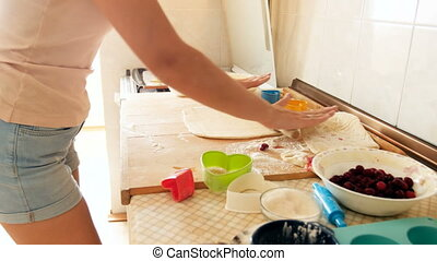 Closeup 4k footage of young woman preparing dough and rolling it with wooden rolling pin on kitchen countertop