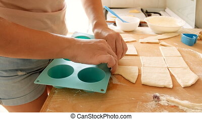 Closeup 4k footage of young woman putting dough pieces in...