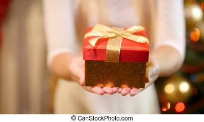 Closeup 4k footage of young woman showing Christmas gift box...
