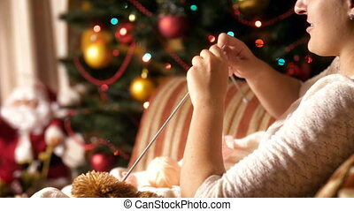 Closeup 4k footage of young woman sitting in armchair next to glowing christmas tree and knitting wool sweater for her children. People relaxing on winter holidays and celebrations at home