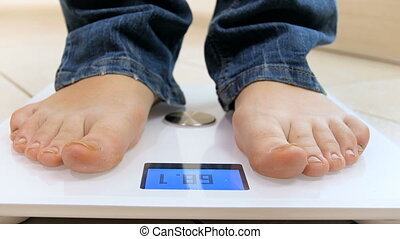 Closeup 4k footage of young woman stepping on weight scales...