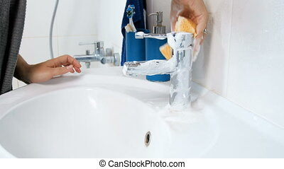 Closeup 4k footage of young woman washing bathroom sing and water tap with detergent and sponge
