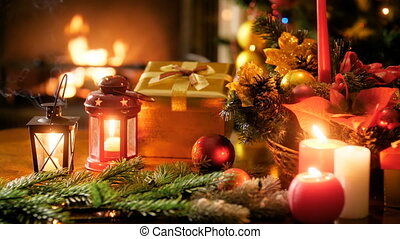 Closeup 4k panning video of burning candles, lanterns, gifts, preents, Christmas wreath and colorful baubles on table against burning fireplace and Christmas tree. Perfect shot for winter celebrations and holidays