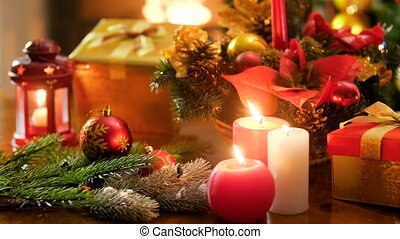 Closeup 4k video of burning candles against colorful baubles, boxes with gifts and presents from Santa and Cristmas wreath. Perfect shot for winter celebrations and holidays