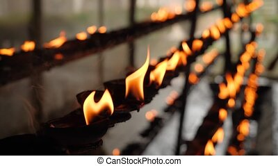 Closeup 4k video of burning oil lamps in the buddhist temple...