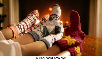 Closeup 4k video of family wearing warm knitted socks resting by the fireplace at living room