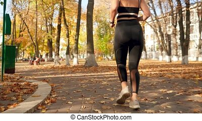 Closeup 4k video of female feet in sneakers while running on...