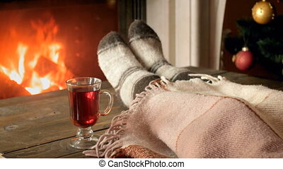 Closeup 4k video of female feet under blanket and cup of tea on wooden table at burning fireplace