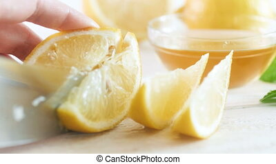 Closeup 4k video of female hand cutting fresh lemons for lemonade on white wooden desk