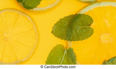 Closeup 4k video of fresh mint leaves and orange slices...