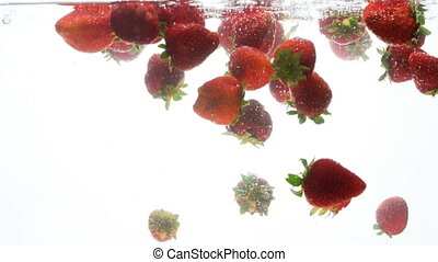 Closeup 4k video of fresh strawberries falling in water...