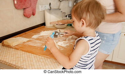 Closeup 4k video of little toddler boy with toy rolling pin helping his mother making pie on kitchen
