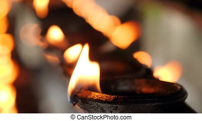 Closeup 4k video of long row of burning oil lamps with ...