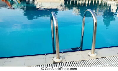 Closeup 4k video of metal ladder at empty swimming pool at...