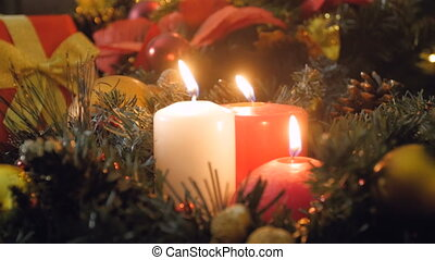 Closeup 4k video of three burning candles in Christmas wreath at night