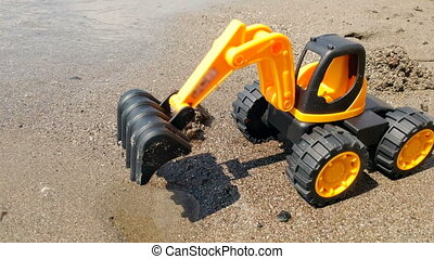 Closeup 4k video of toy orange excavator standing on sand sea beach