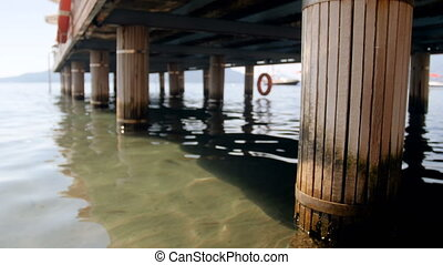 Closeup 4k video of wooden pier with destructed column on...