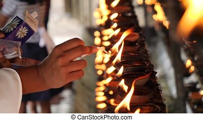 Closeup 4k video of worshipper lighting up the wick of ...