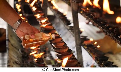 Closeup 4k video of worshipper pouring sacred oil in burning...